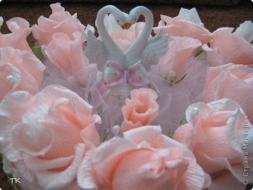 """Вот такое сладкое сердечко я сделала молодожёнам в подарок. В розочках спрятаны конфеты """"Раффаэлло"""", в бутонах- фундук в шоколаде.  Для оформления использовала розовый и белый фатин, бусины, золотую сетку и лебедей. Подарок понравился!    фото 3"""