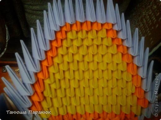 Туловище слоника я начинала делать из 26 модулей. 1, 2, 3, 4 ряд оранжевые модули;  5 ряд - 23 оранжевых и 3 жёлтых;  6 ряд - 22 оранжевых и 4 жёлтых.  7 ряд - 21 оранжевых и 5 жёлтых;  8 ряд - 20 оранжевых и 6 жёлтых;  9 ряд - 19 оранжевых и 7 жёлтых;  10 ряд - 18 оранжевых и 8 жёлтых;  11 ряд - 19 оранжевых и 7 жёлтых;  12 ряд - 18 оранжевых и 8 жёлтых;  13 ряд - 19 оранжевых и 7 жёлтых;  14 ряд - 18 оранжевых и 8 жёлтых;  15 ряд - 19 оранжевых и 7 жёлтых;  16 ряд - 20 оранжевых и 6 желтых;  17 ряд - 21 оранжевый и 5 жёлтых;  18 ряд - 22 оранжевых и 4 жёлтых;  19 ряд - 23 оранжевых и 3 жёлтых;  20,21 ряды все оранжевые модули. Голову тоже начинала делать из 26 модулей. У меня вышло 18 рядов.   Ножки слоника : 1 ряд - 9 жёлтых, 2 ряд - 9 жёлтых, 3 ряд - 9 фиолетовых, 4 ряд - 9 фиолетовых, 5 ряд - 9 оранжевых. Ножки слоника крепила к телу с помощью зубочисток и клея. фото 2