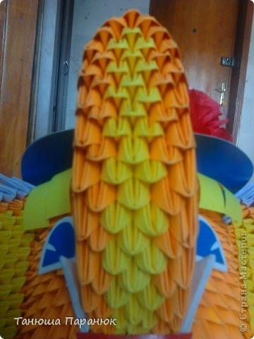 Туловище слоника я начинала делать из 26 модулей. 1, 2, 3, 4 ряд оранжевые модули;  5 ряд - 23 оранжевых и 3 жёлтых;  6 ряд - 22 оранжевых и 4 жёлтых.  7 ряд - 21 оранжевых и 5 жёлтых;  8 ряд - 20 оранжевых и 6 жёлтых;  9 ряд - 19 оранжевых и 7 жёлтых;  10 ряд - 18 оранжевых и 8 жёлтых;  11 ряд - 19 оранжевых и 7 жёлтых;  12 ряд - 18 оранжевых и 8 жёлтых;  13 ряд - 19 оранжевых и 7 жёлтых;  14 ряд - 18 оранжевых и 8 жёлтых;  15 ряд - 19 оранжевых и 7 жёлтых;  16 ряд - 20 оранжевых и 6 желтых;  17 ряд - 21 оранжевый и 5 жёлтых;  18 ряд - 22 оранжевых и 4 жёлтых;  19 ряд - 23 оранжевых и 3 жёлтых;  20,21 ряды все оранжевые модули. Голову тоже начинала делать из 26 модулей. У меня вышло 18 рядов.   Ножки слоника : 1 ряд - 9 жёлтых, 2 ряд - 9 жёлтых, 3 ряд - 9 фиолетовых, 4 ряд - 9 фиолетовых, 5 ряд - 9 оранжевых. Ножки слоника крепила к телу с помощью зубочисток и клея. фото 3