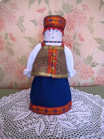 Вот такая красавица получилась у меня. В основе куклы столбик, обшитый тканью. Наряд украшен тесьмой, глаза, нос и рот вышиты нитками. фото 1