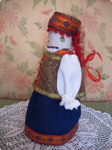 Вот такая красавица получилась у меня. В основе куклы столбик, обшитый тканью. Наряд украшен тесьмой, глаза, нос и рот вышиты нитками. фото 2