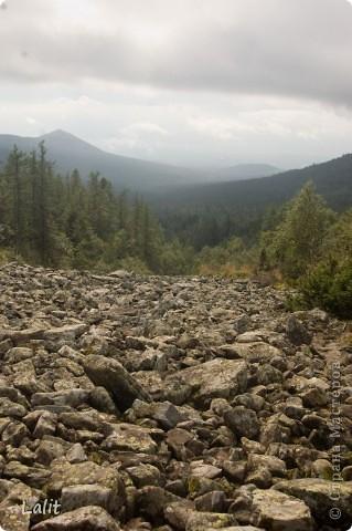 Гора Конжаковский камень (1569 м), север Среднего Урала, находится близ Краснотурьинска. Природа там - не описать словами! Воздух чистейший, виды умопомрачительные! Вот он - седой Урал! Древние ели, поросшие лишайником, вековые кедры, горные реки, поля ягодников на плато...  На Конжаке ежегодно проводится международный марафон 42 км - на вершину горы и обратно по размеченной флажками трассе. Во время марафона спортсмены и просто туристы совершают восхождение на гору за один день, задачу облегчает то, что организаторы обеспечивают питание и питье на всем протяжении трассы. Но обычно на гору ходят с двумя ночевками - на половине подъема ставят палатки и второй день посвящают подъему на вершину.  Итак, начнем. Для начала переправа через горную речку. Сейчас, в августе, она не такая полноводная, много бродов. Река Катышер, приток Лобвы.  Есть и другая дорога, трасса начинается с другой стороны, там приходится переходить через Конжаковку. фото 10
