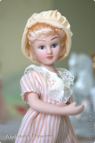 Наряд этой куколки решила кардинально не менять. Сняла шляпку, отгладила ее и пришила тесьму. На рукавах сделала защипы. И приклеила в центр цветочка-брошки бисер. Ну и конечно подправила прическу и контур губ. фото 2