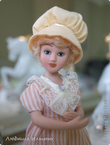 Наряд этой куколки решила кардинально не менять. Сняла шляпку, отгладила ее и пришила тесьму. На рукавах сделала защипы. И приклеила в центр цветочка-брошки бисер. Ну и конечно подправила прическу и контур губ. фото 7