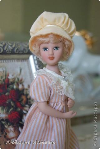 Наряд этой куколки решила кардинально не менять. Сняла шляпку, отгладила ее и пришила тесьму. На рукавах сделала защипы. И приклеила в центр цветочка-брошки бисер. Ну и конечно подправила прическу и контур губ. фото 3