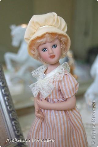 Наряд этой куколки решила кардинально не менять. Сняла шляпку, отгладила ее и пришила тесьму. На рукавах сделала защипы. И приклеила в центр цветочка-брошки бисер. Ну и конечно подправила прическу и контур губ. фото 5