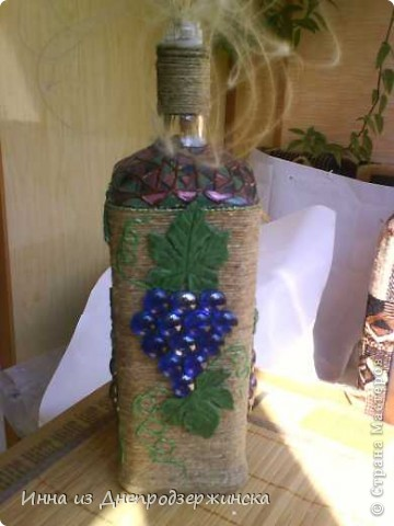 Добрый день! Возникла у меня такая-вот идея! Бутылка обмотана шпагатом на клей ПВА. Листочки из соленого теста,виноградинки- стекляшки .Горлышко бутылки украсила витражом( жемчужный контур, а внутри лак для ногтей). Усики винограда- жемчужный контур(Perlen-Pen). Есть и крышечка, а сейчас просто стоит с Ковыль-травой. фото 2