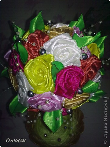 Здравствуй, моя любимая Страна! Здравствуйте, дорогие мастера и мастерицы! Хочу поделиться с вами своим новым достижением - я впервые сделала топиарий!!! Конечно же для любимой мамули в подарок ко дню рождения :)  Пересмотрела в интернете много разных МК по кручению-изготовлению розочек из атласных лент, и выделила для следующий: http://www.youtube.com/watch?v=KwxoubUkxb0 (спасибо за него автору большое-пребольшое!) Розочки, как и в МК по ссылке проклеивала клеем (о нем, кстати, и пойдет речь ниже, аж в самом конце), получается быстро и удобно. Даже ни одной розочки не пробовала прошить нитками... А вот по какому МК делала листики никак не могу найти:(  Основа топиария у меня - шарик для сухого детского бассейна, ствол - деревянная палочка от флажка, горшок - обычный пластиковый для комнатных цветов, только он был просто белый, а я его позолотила. В самом горшочке (девево ,есесина, растет в гипсе) зелень - это пряжа Травка, но ворс у нее длинный и поэтому вся моя трава так лежит, отдыхает. Бусинки, бабочка и кружева - до кучи, чтоб было не так скучно :)))  фото 7