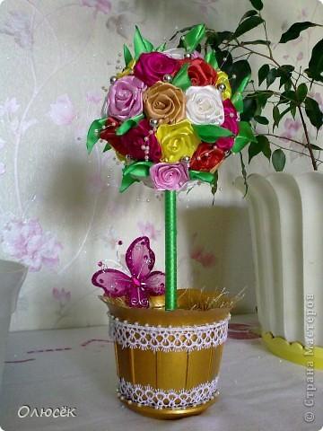 Здравствуй, моя любимая Страна! Здравствуйте, дорогие мастера и мастерицы! Хочу поделиться с вами своим новым достижением - я впервые сделала топиарий!!! Конечно же для любимой мамули в подарок ко дню рождения :)  Пересмотрела в интернете много разных МК по кручению-изготовлению розочек из атласных лент, и выделила для следующий: http://www.youtube.com/watch?v=KwxoubUkxb0 (спасибо за него автору большое-пребольшое!) Розочки, как и в МК по ссылке проклеивала клеем (о нем, кстати, и пойдет речь ниже, аж в самом конце), получается быстро и удобно. Даже ни одной розочки не пробовала прошить нитками... А вот по какому МК делала листики никак не могу найти:(  Основа топиария у меня - шарик для сухого детского бассейна, ствол - деревянная палочка от флажка, горшок - обычный пластиковый для комнатных цветов, только он был просто белый, а я его позолотила. В самом горшочке (девево ,есесина, растет в гипсе) зелень - это пряжа Травка, но ворс у нее длинный и поэтому вся моя трава так лежит, отдыхает. Бусинки, бабочка и кружева - до кучи, чтоб было не так скучно :)))  фото 1