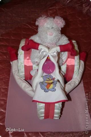 Рождение малышки у подруги сподвигло на первый опыт создания композиции из подгузников. Идея не моя. Нашла в интернете. Удалось смастерить из: подгузники (не менее 40 штук, здесь 80), 2 слюнявчика, 4 пеленки, 2 пары носочков, поильник, игрушка, атласные ленты на крепление колес)))) фото 1