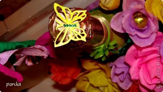 Хочу выставить на ваш суд, дорогие мастерицы, мой первый букет из конфет. Цветы, как оказалось, делать несложно. Хорошо стало получаться со второй конфеты (первый раз я выбрала слишком большую). Для новичков я советовала бы выбирать маленькие круглые конфетки и желательно в золотистой или серебристой обвертке, которые универсально смотрятся в любом цвете лепестков. После 3-го десятка цветов, когда уже появляется определенный опыт, можно и из больших конфет делать. Экспериментировала на разных видах цветов, но розы почему-то всем нравятся больше всего. Конфеты приклеивала к шпажке с помощью двухстороннего скотча, а затем дополнительно укрепляем нитками. В стране есть много МК по выполнению роз из бумаги. Я вырезала отдельно лепесточки, а затем по 3-4 штуки прикрепляла к своему цветку. Как делать бутон и стебель можно посмотреть хороший МК ~ marishka ~ «Мои бутончики роз МК»→ https://stranamasterov.ru/node/354568. Букет сделан на свадьбу подружке. Удобно оформлять в корзине, легче в ней переносить букет и цветы не мнутся. Корзину покупала в цветочном магазине, но вид ее оставлял желать лучшего. Декорировала корзинку с помощью гофробумаги, ткань-сетка, лента. Ручку корзины промазала клеем ПВА и обкрутила сиреневой лентой (можно и гофробумагой). Гофробумагу сложила гармошкой и обкрутила корзину. На дно корзины укладываем пенопласт и формируем букет. фото 4