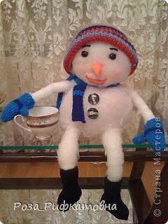 Этот снеговичок живет дома на столе. Чашку я ему дала, чтобы были понятны его размеры. Скомкала из бумаги два шара, обтянула их синтепоном, все как следует обмазала клейстером ( сварила из муки). Связала варежки, валенки, шапочку и шарфик. Нос-морковку  сшила из флиса, глазки-угольки из овальных бусин.  Живет дома, потому и домовичок. Он  мягкий, уютный и очень наивный!