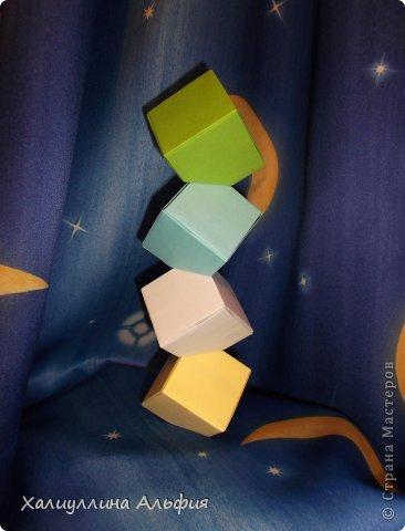 """Вот такую забавную башенку-пирамидку из забавных Кубов Колумба я научилась делать на днях с помощью видеоролика на ютубе (а вот и прямая ссылка на него, если кто-то не очень хорошо разберется в моем фото-МК: http://www.youtube.com/watch?v=6u-1a1UFj_k ). Вся суть заключается  втом, что один из углов кубика собирается, как """"вдавленный"""" внутрь. Благодаря этой конструкционной особенности кубики можно ставить друг на друга, создавая причудливую и интересующую глаз иллюзию. Многие не могут поверить с первого раза, что кубики никак не склеены между собой. фото 1"""