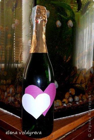 бутылку моем от наклеек... обезжириваем,клеим сердечка... клеим на бутылку розы и листики красим акриловой аэрозольной краской отдираем наклеенные сердечки... контуром подчёркиваем их, рисуем контуром по всей бутылке сердечка,клеим бантик внутри сердец пишем первые буквы имён молодожёнов фото 2