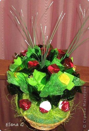 Вот такие мои цветочные полянки. Для основы использовала плетенную корзинку, заполняла пенопластом, который драпировала обыкновенной гофро-бумагой зеленого цвета. Дальше ваша фантазия. В этом букете к стволу цветка крепила тейп-лентой конфетки, которые выполняют роль листиков. Цветы делала из прессованного красного сизаля  фото 3
