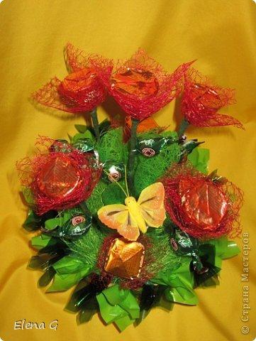 Вот такие мои цветочные полянки. Для основы использовала плетенную корзинку, заполняла пенопластом, который драпировала обыкновенной гофро-бумагой зеленого цвета. Дальше ваша фантазия. В этом букете к стволу цветка крепила тейп-лентой конфетки, которые выполняют роль листиков. Цветы делала из прессованного красного сизаля