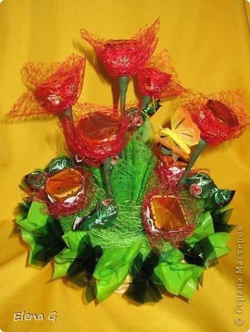 Вот такие мои цветочные полянки. Для основы использовала плетенную корзинку, заполняла пенопластом, который драпировала обыкновенной гофро-бумагой зеленого цвета. Дальше ваша фантазия. В этом букете к стволу цветка крепила тейп-лентой конфетки, которые выполняют роль листиков. Цветы делала из прессованного красного сизаля  фото 2