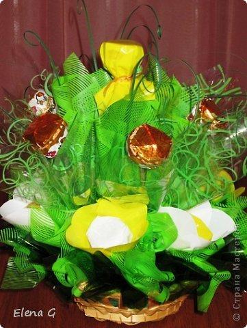 Вот такие мои цветочные полянки. Для основы использовала плетенную корзинку, заполняла пенопластом, который драпировала обыкновенной гофро-бумагой зеленого цвета. Дальше ваша фантазия. В этом букете к стволу цветка крепила тейп-лентой конфетки, которые выполняют роль листиков. Цветы делала из прессованного красного сизаля  фото 4