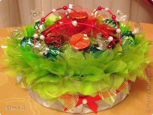 Вот такие мои цветочные полянки. Для основы использовала плетенную корзинку, заполняла пенопластом, который драпировала обыкновенной гофро-бумагой зеленого цвета. Дальше ваша фантазия. В этом букете к стволу цветка крепила тейп-лентой конфетки, которые выполняют роль листиков. Цветы делала из прессованного красного сизаля  фото 5