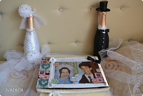 Ну вот и готовы подарки на годовщину свадьбы моего свёкра и свекрови. Прошло уже столько лет, а они по прежнему очень любят друг друга. Поэтому и напиток я украсила как на настоящую свадьбу в традиционных цветах. В коробочке с  их фотографией лежит картина, которую я сделала раньше с помощью советов и работ на нашем сайте.
