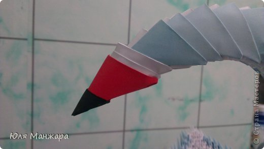 """Вот такой вот лебедь получается в конце работы) А теперь приступим к изготовлению. Нам понадобятся:  *бумага   """"голубая - 145 модулей А4/8 (19 листов)   """"синяя - 85 модулей А4/8 (11 листов)   """" красная - 1 модуль А4/8   """"черная - 1 модуль А4/32   """"белая - 1175 модулей А4/8 (147 листов)   """"светло желтая - 5 полосок шириной 5 мм   """"желтая - 10 полосок шириной 5 мм   """"оранжевая - 10 полосок шириной 5 мм   """"зеленая - 16 полосок шириной 5 мм *клей ПВА *бантик *ленточка *стразы *иголка  фото 24"""