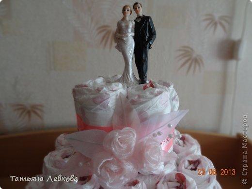 Сестра попросила сделать тортик из памперсов на свадьбу. И вот что у меня получилось. Сестре очень понравился, надеюсь, молодожёнам он тоже понравится. На тортик у меня ушло 65 памперсов.В середине тортика - бутылка. Для подставки использовала блюдо, сверху застелила его салфетками. Открытка покупная. фото 2