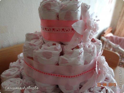Сестра попросила сделать тортик из памперсов на свадьбу. И вот что у меня получилось. Сестре очень понравился, надеюсь, молодожёнам он тоже понравится. На тортик у меня ушло 65 памперсов.В середине тортика - бутылка. Для подставки использовала блюдо, сверху застелила его салфетками. Открытка покупная. фото 3
