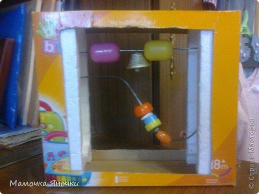 Вот такую игрушку соорудила я для дочки из того, что было, как говорится. Вырезала середину коробки, вставила по краям пенопласт, в него воткнула металлические пруты (от раскладной сушилки для белья), а на низ нанизала то, что нашлось дома: крышки, ракушку, бусины, яички от киндеров (внутри бусинки), колокольчик. фото 1