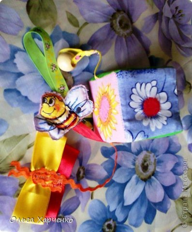 Кубик 8х8 см. Ткань, паролон, погремушка, ленты разные, деревянная бусина. Бабочка и шмель на лентах и с липучкой. Летают к цветам- серединки ромашки и подсолнуха тоже липучка. Внутри кубика погремушка. фото 1