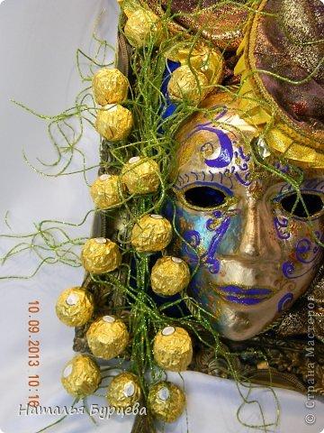"""Здравствуйте, еще раз). Конкурсная работа, занявшая 2 место, чем я несказанно горжусь)))! Не ожидала, если честно! """"ТАИНСТВЕННАЯ ВЕНЕЦИЯ""""   Издревле венецианские маски использовались для сокрытия личности людьми. Появившись несколько веков назад в Венеции, эти характерные маски делались из папье-маше и обильно украшались мехом, тканями, драгоценными камнями и перьями. Со временем маски стали символом Карневале (Венецианского карнавала) — пышной процессии или уличной ярмарки. Истоки венецианского карнавала уходят глубже — в древние римские Сатурналии — ежегодные праздники в честь бога Сатурна, которые справлялись в декабре после уборки урожая во время зимнего солнцестояния и сопровождались массовыми гуляниями. Рабов сажали за общий стол, и чтобы сгладить неловкость необычной ситуации, все надевали маски. Создание маски это зачастую медленный и кропотливый процесс, с использованием дорогих материалов. Здесь все зависит от фантазии художника. Цены на такие шедевры часто поражают воображение не меньше, чем их внешний вид!  Использованные материалы: Конфеты Фереро Роше - 15 шт. Конфеты снимаются, не нарушая целостности композиции. Шифон, бархат, стразы, боа, павлинье перо, парчовая лента, глиттеры, контуры Декола, искусственные вставки, покрытые глиттером; заготовка маски из папье-маше, рама.   фото 5"""