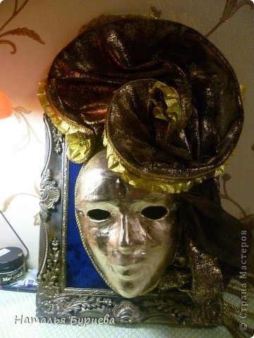 """Здравствуйте, еще раз). Конкурсная работа, занявшая 2 место, чем я несказанно горжусь)))! Не ожидала, если честно! """"ТАИНСТВЕННАЯ ВЕНЕЦИЯ""""   Издревле венецианские маски использовались для сокрытия личности людьми. Появившись несколько веков назад в Венеции, эти характерные маски делались из папье-маше и обильно украшались мехом, тканями, драгоценными камнями и перьями. Со временем маски стали символом Карневале (Венецианского карнавала) — пышной процессии или уличной ярмарки. Истоки венецианского карнавала уходят глубже — в древние римские Сатурналии — ежегодные праздники в честь бога Сатурна, которые справлялись в декабре после уборки урожая во время зимнего солнцестояния и сопровождались массовыми гуляниями. Рабов сажали за общий стол, и чтобы сгладить неловкость необычной ситуации, все надевали маски. Создание маски это зачастую медленный и кропотливый процесс, с использованием дорогих материалов. Здесь все зависит от фантазии художника. Цены на такие шедевры часто поражают воображение не меньше, чем их внешний вид!  Использованные материалы: Конфеты Фереро Роше - 15 шт. Конфеты снимаются, не нарушая целостности композиции. Шифон, бархат, стразы, боа, павлинье перо, парчовая лента, глиттеры, контуры Декола, искусственные вставки, покрытые глиттером; заготовка маски из папье-маше, рама.   фото 13"""