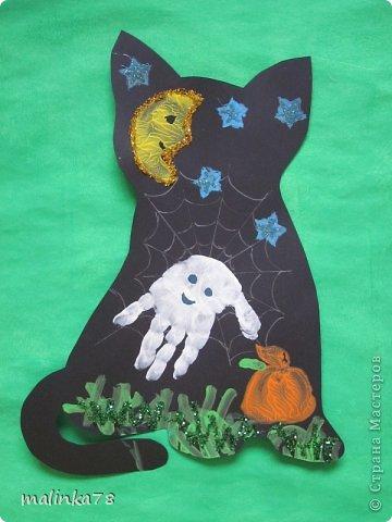 Пришла мне в голову идея сделать с детками вот таких кошек. Вырезаем из чёрной бумаги силуэт кошек и на них рисуем паутинку и  делаем отпечаток ладошки- это приведение, и так же делаем штамп тыквы, луны и звёзд. Травки дети рисовали ватными палочками. фото 3