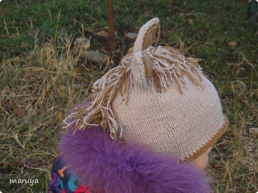 вот такая лошадка - символ этого года у меня вышла на подарки. пока майя была в настроении решила по-фоткать на ней)) вязала шапку сверху вниз, на кольцевых спицах. ушло чуть меньше 100 грамм. и темная нить для отделки. ушки двойные задник из светлых ниток, перед из темных. сшиты и пришиты))) гриву делала из нарезанных ниток привязанных на косичку связанную крючком. потом пришила к шапке фото 2