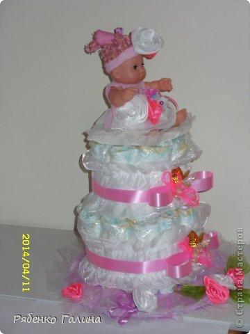 """на два яруса тортик, памперсы оборачивала в пищевую пленку, 27 шт. Ярусы стоят на картонной подставке, декорированной пленкой и тканью, в средине стержень держит""""коржи"""" и на него я приклеила маленькой капелькой подложку в виде цветочка для куклы (на ней она сидит) фото 4"""