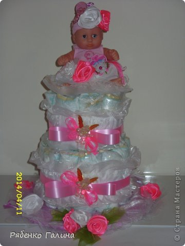 """на два яруса тортик, памперсы оборачивала в пищевую пленку, 27 шт. Ярусы стоят на картонной подставке, декорированной пленкой и тканью, в средине стержень держит""""коржи"""" и на него я приклеила маленькой капелькой подложку в виде цветочка для куклы (на ней она сидит) фото 1"""