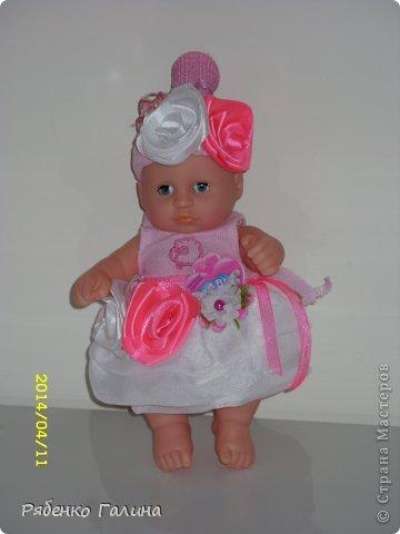 """на два яруса тортик, памперсы оборачивала в пищевую пленку, 27 шт. Ярусы стоят на картонной подставке, декорированной пленкой и тканью, в средине стержень держит""""коржи"""" и на него я приклеила маленькой капелькой подложку в виде цветочка для куклы (на ней она сидит) фото 5"""
