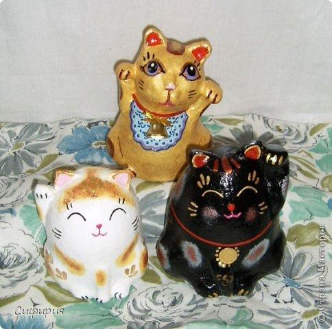 """Здравствуйте, жители Страны Мастеров! Хочу вам показать японские кошечки-статуэтки, которые приносят удачу и благополучие своим владельцам. Maneki Neko ( 招き猫 ) - буквально означает """"Приглашающий Кот"""", """"Зовущая Кошка"""", также известный как """"Кот Счастья"""", """"Денежный Кот"""" или """"Кот Удачи"""". Манеки Неко — это популярный японский талисман удачи, вылепленный из глины или папье-маше в виде сидящей кошки, передняя лапка которой, поднята вверх. Манеки Неко — символ удачи, счастья, домашнего тепла, уюта и благополучия. Поднятая вверх лапка приманивает эти радости в дом. Располагать статуэтки котов лучше всего парами. фото 1"""