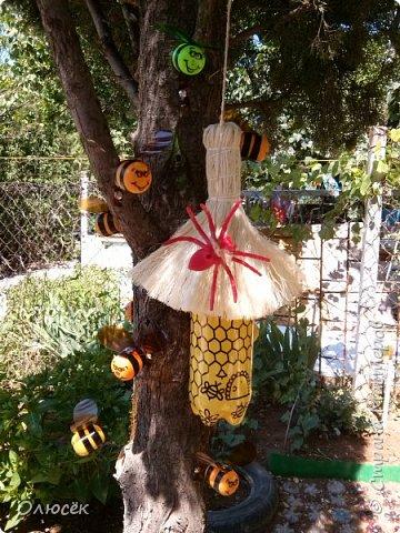 Такой улик и рой пчел сделали с мужем доченьке в садик для площадки еще в прошлом году.  Улик - это двухлитровый пак от сока, обернутый золотистой подарочной бумагой. Крыша - сетка от букета цветов (как правильно называется- не знаю). Пчелки - желтки от киндеров, полоски -черная изолента, крылышки - из пластиковых бутылок. Раскрашено перманентным маркером. фото 7