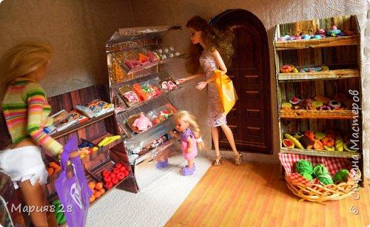 Идея магазина для кукол зрела очень давно, в предыдущих записях я делала несколько мастер-классов как сделать витрину, кассу и вешалку. Изначально задумывался магазин одежды. Но за зиму мы с дочкой открыли для себя ЛЕПКУ ИЗ СОЛЕНОГО ТЕСТА и столько всякой еды налепили для куколок, что я решила сделать магазин, который можно превращать как в магазин одежды так и в магазин продуктов. Первым делом из большой коробки я сделала само помещение-комнату, в которой будет размещаться магазин. С большим окном-витриной слева и открывающейся дверью справа. Пол я оклеила распечатками с паркетом, а стены остатками обоев. Для витринного окошка отлично подошел кусок пластика от коробки с какой-то игрушкой. фото 1