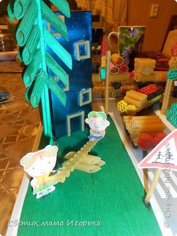 """Добрый день!  Хотела бы показать одну из наших последних работ, выполненных для конкурса в детском саду.  Тема """"Правила дорожного движения"""". Условия выполнение - материал любой, размер работы 30*30 см.  В качестве материалы были выбраны макароны. Между собой все крепилось на горячий клей, а к основе - на клей момент.   Их использованных материалов так же понадобились: досочка (основа), гофрированная бумага (полянки), скотч (бордюры, пешеходка), коробка из под чая (дом), металлизированная бумага (дом), гуашь (окраска макарон), распечатанные детишки и знаки.  Что делал Игорь: красил макарошки гуашью, помогал собирать паровоз, фонтан и машинки, а так же делал расстановку персонажей))))  Затраты по времени - не измерены до конца, потому как красилось и собиралось все по чуть-чуть вечерами минут по 30-40 в течении недели. Зато свести все в композицию удалось за пару вечеров с учетом всех доделок.  Результатом я не вполне довольна и свои косяки вижу, но всегда рада услышать мнение со стороны! Далее фото. Вид спереди. Хорошо видны играющие детишки и парочка, переходящие дорогу по правилам ))) фото 3"""