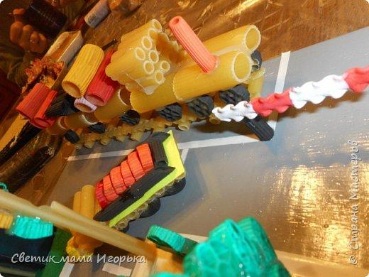 """Добрый день!  Хотела бы показать одну из наших последних работ, выполненных для конкурса в детском саду.  Тема """"Правила дорожного движения"""". Условия выполнение - материал любой, размер работы 30*30 см.  В качестве материалы были выбраны макароны. Между собой все крепилось на горячий клей, а к основе - на клей момент.   Их использованных материалов так же понадобились: досочка (основа), гофрированная бумага (полянки), скотч (бордюры, пешеходка), коробка из под чая (дом), металлизированная бумага (дом), гуашь (окраска макарон), распечатанные детишки и знаки.  Что делал Игорь: красил макарошки гуашью, помогал собирать паровоз, фонтан и машинки, а так же делал расстановку персонажей))))  Затраты по времени - не измерены до конца, потому как красилось и собиралось все по чуть-чуть вечерами минут по 30-40 в течении недели. Зато свести все в композицию удалось за пару вечеров с учетом всех доделок.  Результатом я не вполне довольна и свои косяки вижу, но всегда рада услышать мнение со стороны! Далее фото. Вид спереди. Хорошо видны играющие детишки и парочка, переходящие дорогу по правилам ))) фото 4"""