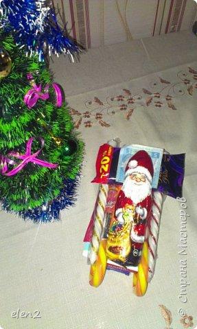 Сделала сладкие саночки  в подарок на День Святого Николая для внучки: Использовала для саней   предметы и  все соединила тонким скойчем полозья- это сладкие леденцы Снизу прицепила на скойч 2 пачки бенгальских огней. По бокам - 2 красивые,ароматизированные свечечки на новый год А в саночки уложила все, что моя внучка любит: шоколадку, желе(упаковочка),разноцветные ручки, 2 блокнотика в школу,влажные салфетки (написано антимикробные),денежки и шоколадного Деда Мороза. фото 2