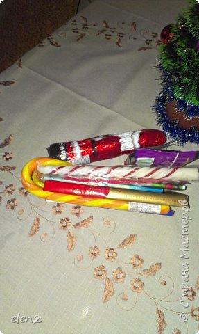 Сделала сладкие саночки  в подарок на День Святого Николая для внучки: Использовала для саней   предметы и  все соединила тонким скойчем полозья- это сладкие леденцы Снизу прицепила на скойч 2 пачки бенгальских огней. По бокам - 2 красивые,ароматизированные свечечки на новый год А в саночки уложила все, что моя внучка любит: шоколадку, желе(упаковочка),разноцветные ручки, 2 блокнотика в школу,влажные салфетки (написано антимикробные),денежки и шоколадного Деда Мороза. фото 3