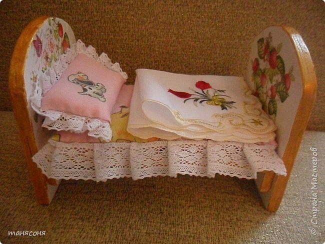 Здравствуйте! Моя дочка ещё совсем маленькая, но мы уже начинаем играть в куклы. Кормим их, укладываем спать. В магазинах кроватки слишком хлипкие, а мы ещё не особо нежные. Поэтому я решила сделать кроватку поосновательней. Муж сделал заготовку из фанеры, я её задекорировала, сшила матрасик с подушкой, над одеялом ещё нужно поработать, но пока мы играем так.  фото 6