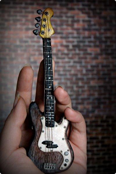 """Доброго времени суток!  Так сложилось, что практически все мои кукло-парни музыканты, а найти красивую и качественную модель гитары формата 1:6 достаточно тяжело (да и затратно). Поэтому я решила создать инструменты своими руками. Нужно отметить что до """"гитарных"""" опытов я полимерку в руках держала всего один раз.     Первой стала бас-гитара FENDER SQUIER AFFINITY PRECISION BASS для  моего любимого Сида. Если найти модель соло-гитары еще можно, то найти модель басухи почти нереально(я знаю, я пробовала).  За основу брала МК Сашули-красотули http://stranamasterov.ru/node/293031?c=favorite , за который ей огромное спасибо и низкий поклон!  Гитара выполнена из полимерной глины, струны и порожки на грифе -проволока, датчики на звукоснимателях- микробисер     фото 3"""