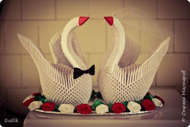 Вот, нашла фотографию и решила похвастаться)) Делала этих лебедей еще в 2012 году на свадьбу подруги. Собрала 2 лебедей, прицепила галстук-бабочку для жениха и фату с короной для невесты. Подумала, что чего-то не хватает и решила посадить пару на озеро. Обклеила картон фольгой, скрутила розочки из лент и наклеила по краю, уложила зеленую ленту простыми петельками. И вот что получилось) После свадьбы всю композицию обернули прозрачной пленкой, чтобы не пылилась, надеюсь, живы мои красавцы еще) Может кому-то эта идея пригодится, смотрится красиво)