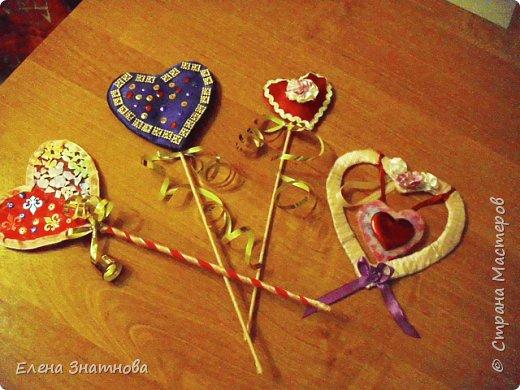 Здравствуйте друзья! Хочу показать несколько поделок к дню святого Валентина. Такие поделки могут сделать дети с 6 лет, более сложные – при помощи взрослых.  Дети с удовольствием участвуют в творческом процессе, им немного нужно дать выразить свою фантазию. Поэтому я всегда предлагаю несколько вариантов и поддержу их с новыми идеями. Валентинки – сердечки на шпажках: каркас гофрированный картон, обтянут атласным шёлком, выглядит как подушечка, внутри синтепон обратной стороны: плоская часть. Все стороны сердечек оформлены по-разному,  подушечка  - в основом цветами из лент, обратная сторона – всякой всячиной, всё, что можно приклеить на клей карандаш. На одной из валентинок сторона обклеена яичной скорлупой и подкрашена хаотично акварелью и блёстками. Валентинки на шпажках. Шпажки обмотаны узкой тесьмой. Палочки просто протыкаются в сердечки, продвигаются в отверстия гофрированного картона, поэтому заготовка из гофрированного картона лучше делать по вертикальным линиям и заранее проткнуть шпажкой. В заключении - на шпажке завязан бант из металлизированной ленты, придаёт праздничный вид. фото 1