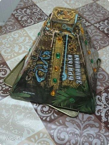 Доброе время суток всем мастерам! Вот такая кормушка для птиц получилась у меня из жестяной коробочки-пирамидки от новогоднего подарка, который был получен в цирке. Так сказать, от братьев Запашных- на крышке так и написано.  Мне понадобились: коробка от подарка, фанерка, шнур бельевой, стакан от блендера, палочки бамбуковые, бусины деревянные, клей-секунда, клей-титан,  дрель,  бутылка пластиковая с крышкой, скрепки и конечно же семечки! фото 2