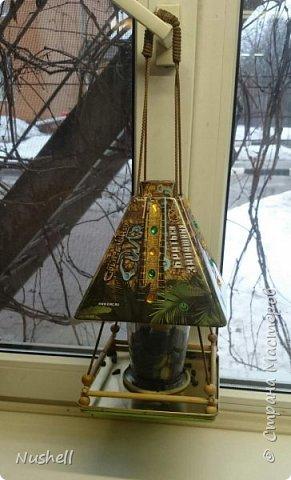 Доброе время суток всем мастерам! Вот такая кормушка для птиц получилась у меня из жестяной коробочки-пирамидки от новогоднего подарка, который был получен в цирке. Так сказать, от братьев Запашных- на крышке так и написано.  Мне понадобились: коробка от подарка, фанерка, шнур бельевой, стакан от блендера, палочки бамбуковые, бусины деревянные, клей-секунда, клей-титан,  дрель,  бутылка пластиковая с крышкой, скрепки и конечно же семечки! фото 8