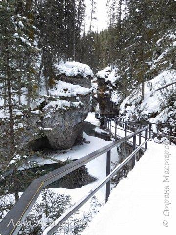 Добрый всем зимний денек! В этот раз хочу рассказать о нашей поездке зимой в горы. Мы вообще редко зимой ездим, но уж больно в этом году теплая зима. Недавно выбрались в Johnston Canyon, это недалеко от Банфа, было тепло и мы прекрасно погуляли. Посмотрели на скалолазах лазающих по ледовым стенкам замерзшего водопада.  Ни разу не были там зимой - очень красиво, правда дорога скользкая, дети половину пути проехали по льду... Дорога вдоль каньона проложена с перилами, так что идти было удобно.  фото 1